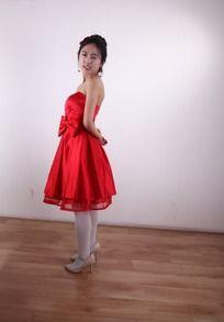 双手上背到身后红色礼服的美女