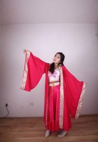 双臂展开跳舞的穿红色戏服的女人