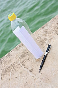 钢笔与装信笺的漂流瓶