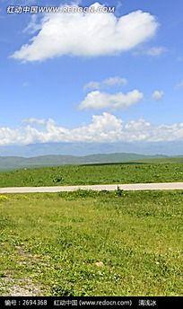 一条横穿在蓝天白云绿草间的路