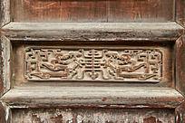 破旧的木门面上雕刻马赛克龙纹图案
