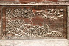 破旧的木门面上雕刻松鹤吉祥图案