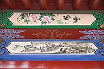 古建筑上彩绘双飞的燕子和山水画