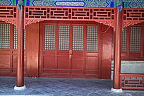 园林里古建筑上的红色中式雕刻彩绘门窗和雕刻角花图片