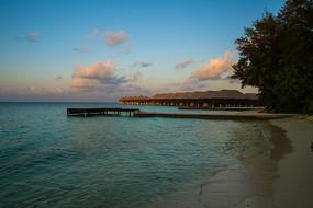 马尔代夫Coco岛日出时分的蓝天白云大海沙滩和海滨木屋