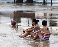 几位女青年坐在沙滩上