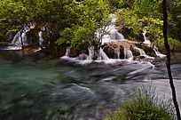 树林中小瀑布汇成的蓝色水流