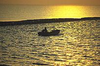 金色海面上准备出海的渔民