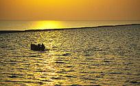 金色海面行驶的渔船