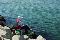 碧蓝海水边的钓鱼人