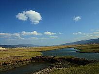 蓝天白云下的草原与河流