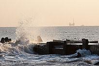 日出海边打在堤坝上的海浪与远处的钻井平台