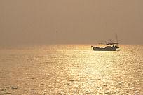 日出时刻金色海面的一条渔船