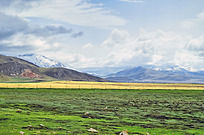 雪山下黄绿相间的草原