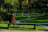 夕阳下的坐在长椅上的女性