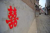 山村里办喜事贴在胡同墙壁上的大红双喜字