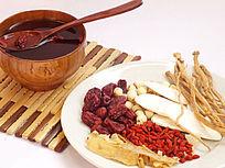 一盘滋补药材和一个木碗汤药图片