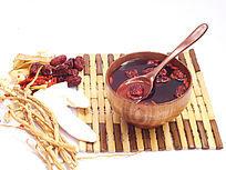 滋补药材和一个木碗汤药图片