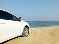 停靠在海滩上的白色汽车图片