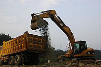 挖掘机为大货车装沙土