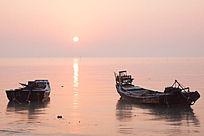 日出时海边的2艘渔船