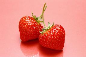 粉红背景下的两草莓