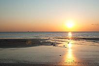 太阳升起后金色的阳光照在退潮的海边滩涂上