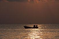 金色海面上行驶的渔船