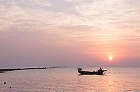 迎着日出出海的渔民