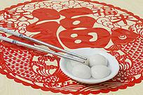 近摄中国剪纸上放着一双筷一碗汤圆图片