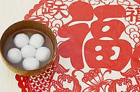 近摄中国剪纸上放着一碗汤圆特写