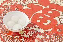 近摄中国剪纸上放着一碗汤圆图片