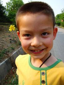耳朵上戴着花开心的笑了的男孩