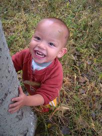 抱着树开心的笑的孩子