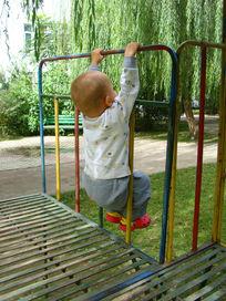手抓铁栏杆锻炼身体的孩子