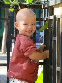 手抓着栏杆开心笑的孩子