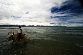 西藏高原湖泊骑牦牛的藏民