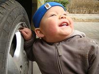 手扶轮胎开心笑的孩子