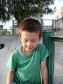靠着绿网低头沉思的孩子