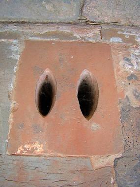 墙壁上的通风口的石雕猪鼻子