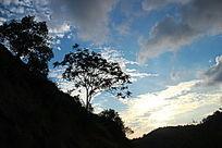 夕阳映衬下的蓝天白云和山岭树木
