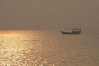 日出时刻金色海面上行驶的渔船