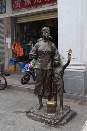 一个小孩和一个女人站着的雕塑