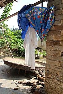 阳光下农家小院悬挂着的白衬衣和蓝色花伞