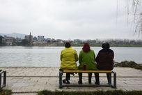 河边长椅上休息的三个人