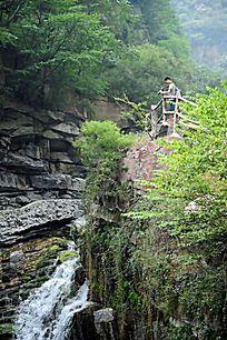 和朋友重游九莲山风景区在护栏外拍摄峡谷中的小瀑布
