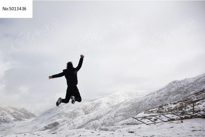 雪山上跳跃的人图片