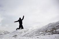 雪山上跳跃的人