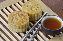 中国美食二个中秋月饼和一杯红茶特写图片