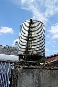 屋顶上长着青苔的不锈钢储水塔